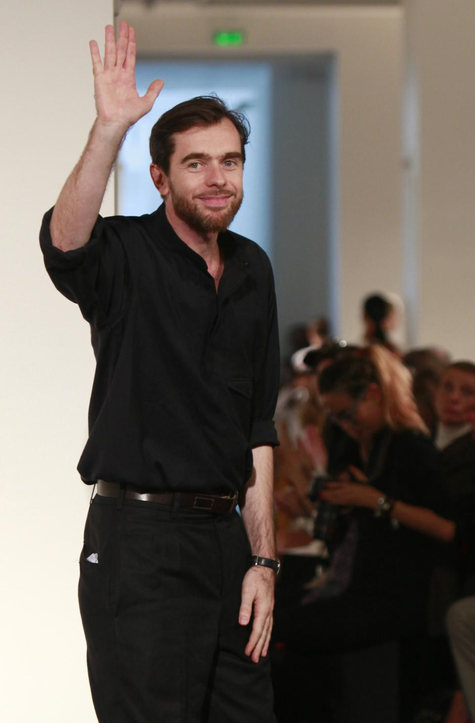 French fashion designer Christophe Lemaire waves after the presentation of Hermes' ready to wear Spring-Summer 2013 collection, presented in Paris, Sunday, Sept.30, 2012. (AP Photo/Thibault Camus)