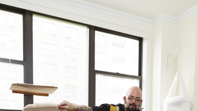 """In this photo taken in late May 2012, cat behaviorist Jackson Galaxy is shown working with Oliver the cat, during production of Season 3 of Animal Planet's, """"My Cat From Hell,"""" in New York. On his TV show, he helps cats and cat owners solve behavior problems, human and feline. (AP Photo/Animal Planet)"""