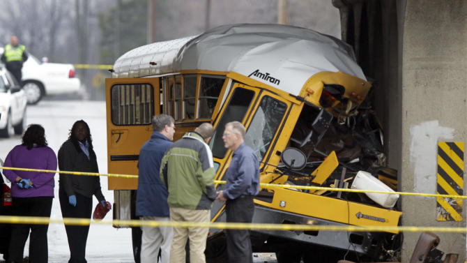 Investigators look over the scene of a fatal bus crash on the southeast side of Indianapolis, Monday, March 12, 2012. The driver and one student were killed and two other critically injured. (AP Photo/Michael Conroy)