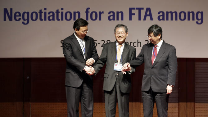South Korean chief negotiator Choi Kyong-lim, center, his Japanese counterpart Koji Tsuruoka, right, and Chinese counterpart Yu Jianhua, left, hold hands each other at a photo call before their talks in Seoul, South Korea, Tuesday, March 26, 2013. Senior officials of three countries met at the first round of negotiations for a Free Trade Agreement (FTA) which starts here from March 26 to 28. (AP Photo/Lee Jin-man)
