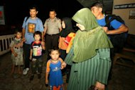 <p>A group of Australia-bound Afghan asylum seekers is seen arriving at a police station in Malang town, East Java province, in April. Australia has struggled to cope with a record influx of boatpeople this year, many originally from Afghanistan, Sri Lanka, Iran and Iraq who make their way to Australia via Asia.</p>