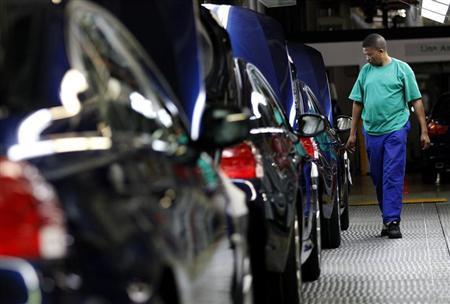 A worker walks near a row of cars at BMW's manufacturing plant in Rosslyn, outside Pretoria
