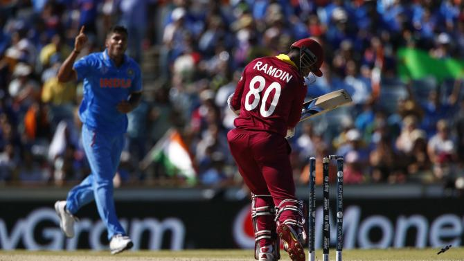 West Indies batsman Denesh Ramdin is bowled by India's Umesh Yadav during their Cricket World Cup match in Perth