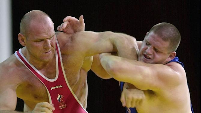 FILE - In this Sept. 27, 2000 file photo, Rulon Gardner, right, of the United States, holds the arm of Alexander Karelin of Russia during the final bout in the 130 kg class of Greco-Roman wrestling event at the Summer Olympic Games in Sydney. Gardner's epic upset of Russian wrestling great Alexander Karelin in 2000 remains one of the most compelling moments of the modern Olympics. Starting in 2020, youngsters looking to Gardner and Karelin for inspiration won't have a chance to excel on the sport's biggest stage. Gardner and nearly everyone else associated with the sport in the U.S. were jolted Tuesday, Feb. 12, 2013 when International Olympic Committee leaders dropped wrestling from the Summer Games. (AP Photo/Katsumi Kasahara, File )
