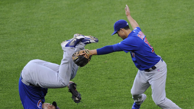 Chicago Cubs first baseman Anthony Rizzo, left, rolls after he caught a pop fly by Washington Nationals' Ryan Zimmerman during the eighth inning of a baseball game, Saturday, May 11, 2013, in Washington. Second baseman Darwin Barney is at right. The Cubs won 8-2. (AP Photo/Nick Wass)