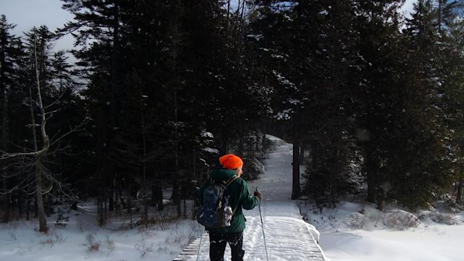 This December 2012 photo shows Lynn Dombek cross-country skiing over a bridge on the Lodge to Lodge trail between camps at the Appalachian Mountain Club's backcountry wilderness lodge near Greenville, Maine. In winter, visitors can reach the lodges and cabins only by cross-country skiing in.   (AP Photo/Donna Lawlor)