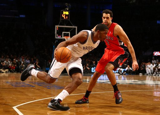 NEW YORK, NY - JANUARY 15:  Brooklyn Nets shooting guard Joe Johnson #7 drives against Toronto Raptors small forward Landry Fields #2 during their game at the Barclays Center on January15, 2013 in the Brooklyn borough of New York City. (Photo by Al Bello/Getty Images)