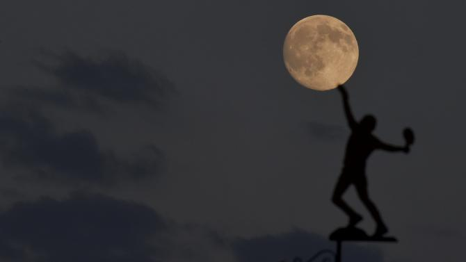 The moon rises above the weather vane at the All England Lawn Tennis and Croquet Club which hosts the Wimbledon Tennis Championships in London