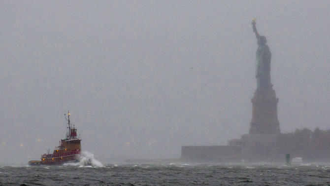 FILE - In a Monday, Oct. 29, 2012 file photo, waves crash over the bow of a tug boat as it passes near the Statue of Liberty in New York as rough water as the result of Hurricane Sandy churns the waters of New York Harbor. The Statue of Liberty survived Superstorm Sandy intact. But the storm flooded Liberty Island's power and heating systems and damaged its buildings. Superintendent David Luchsinger, who led reporters on a tour of Liberty Island on Friday, Nov. 30, 2012, says the National Park Service still does not know when the statue will reopen to the public or how much the island repairs will cost.  (AP Photo/Craig Ruttle, File)