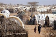 """People move around near makeshift homes, or """"tukuls"""", in the outskirts of Dagahaley settlement at Kenya's Dadaab Refugee Camp, situated northeast of the capital Nairobi, near the Somali border, August 31, 2011. REUTERS/Jonathan Ernst"""