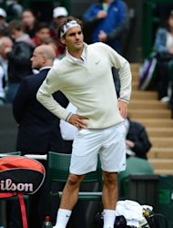 Switzerland's Roger Federer keeps warm during a delay in his fourth round men's singles match against Belgium's Xavier Malisse on day seven of the 2012 Wimbledon Championships at the All England Tennis Club in Wimbledon, southwest London. Federer won 7-6 (7/1), 6-1, 4-6, 6-3