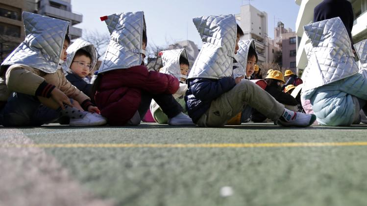 Kindergarten students sit in a playground during an earthquake simulation exercise at an elementary school in Tokyo