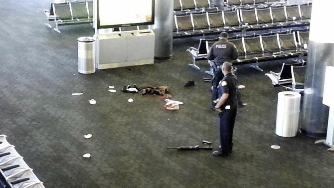 FILE - In this Nov. 1, 2013 file photo provided to the AP, which has been authenticated based on its contents and other AP reporting, police officers stand near a weapon at the Los Angeles International Airport after a gunman opened fire in the terminal, killing one person and wounding several others. Dispatchers at Los Angeles International Airport who received an emergency call seconds after the gunman opened fire in a passenger screening area last fall didn't know where to send help because the airport's communications system doesn't identify locations of its emergency phones. (AP Photo, File)