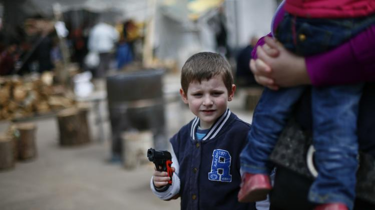 Boy with toy gun passes by in front of barricades at the police headquarters in Slaviansk