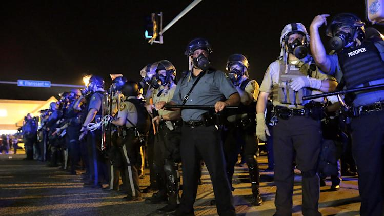 Police is riot gear work to disperse a crowd of protesters Monday, Aug. 18, 2014, in Ferguson, Mo. The protests were sparked after Michael Brown, an unarmed black man was shot and killed by Darren Wilson, a white Ferguson police officer on Aug. 9, 2014. (AP Photo/Jeff Roberson) rder Monday. (AP Photo/Jeff Roberson)