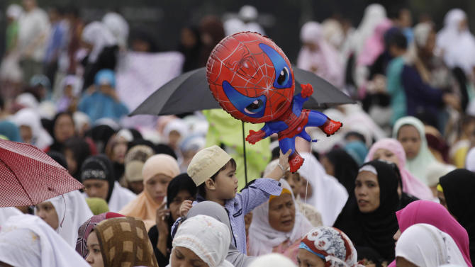 A Filipino Muslim boy plays with a balloon as they celebrate Eid-al Fitr at Manila's Rizal Park, Philippines on Sunday Aug. 19, 2012. Eid al-Fitr marks the end of the holy month of Ramadan. (AP Photo/Aaron Favila)