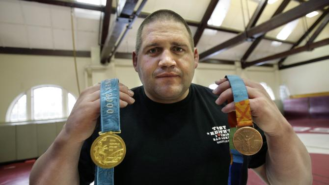 FILE - In this Feb. 27, 2007, file photo, Rulon Gardner holdslding his gold and his bronze Olympic medals after giving a motivational talk to students and faculty at the Middlesex School in Concord, Mass. In yet another setback for Gardner once lauded as the most decorated athlete in the history of American Greco-Roman wrestling, the Olympic gold medalist has filed for bankruptcy. (AP Photo/Michael Dwyer, File)