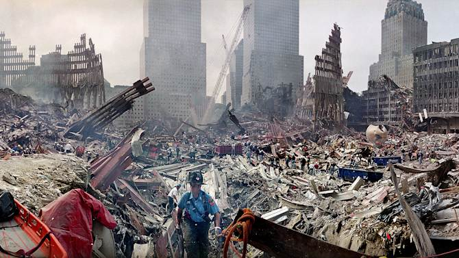 FILE - In this Monday, Sept. 24, 2001 file photo, rescue workers examine the site of the Sept. 11, 2001 World Trade Center terrorist attacks in New York. Several experts say there's no hard evidence to support the federal government's declaration this month that 50 kinds of cancer could be caused by exposure to World Trade Center dust. The decision could help hundreds of people get payouts from a multibillion-dollar World Trade Center health fund to repay those ailing after they breathed in toxic dust created by the collapsing twin towers on Sept. 11, 2001.(AP Photo/Ted S. Warren, Pool, File)