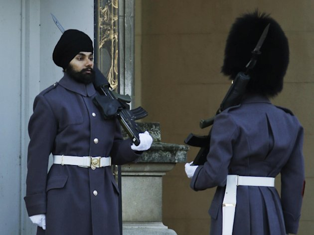 An officer, right, checks Jatinderpal Singh Bhullar, 25, a Sikh soldier with the Scots Guards, performs guarding duties outside Buckingham Palace in central London, Tuesday, Dec. 11, 2012. becoming th