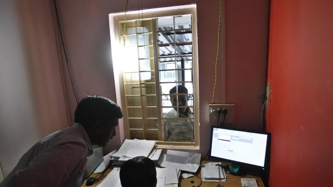 In this Dec. 5, 2012 photo, a man, right, waits to get a copy of a land record at Bhoomi, a program that digitized Karnataka state's 20 million handwritten land records, kiosk in Tumkur 70 Kilometers (43 miles) from Bangalore, India. For years, Karnataka's land records were a quagmire of disputed, forged documents maintained by thousands of tyrannical bureaucrats who demanded bribes to do their jobs. In 2002, there were hopes that this was about to change. (AP Photo/Aijaz Rahi)
