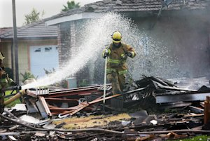 Riverside firefighters work to secure the remains of…