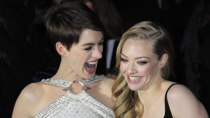 Anne Hathaway and Amanda Seyfried laugh together as they arrive on the red carpet for the World Premiere of 'Les Miserables' at a central London cinema in Leicester Square, Wednesday, Dec. 5, 2012. (Photo by Joel Ryan/Invision/AP)