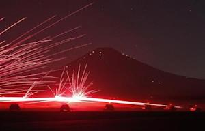 Tracer bullets ricochet off their targets as the Japanese Ground Self-Defence Force Type 74 and Type 90 armoured tanks fire machine guns during a night annual training session in Japan