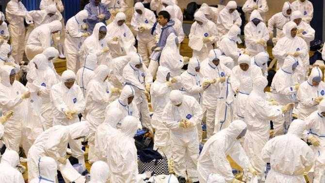 Prefectural government employees and other workers put on protective suits to cull chickens in Taragi town, Kumamoto prefecture