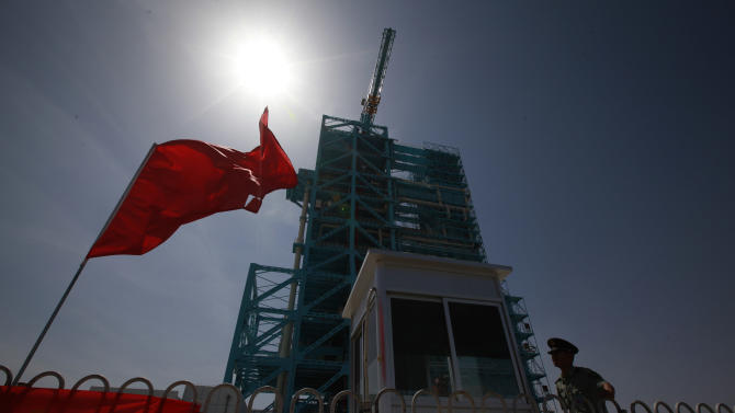 A Chinese soldier is silhouetted near the Shenzhou 9 spacecraft rocket launch pad at the Jiuquan Satellite Launch Center near Jiuquan in western China's Gansu province, Saturday, June 16, 2012. China will send its first woman and two other astronauts into space Saturday to work on a temporary space station for about a week, in a key step toward becoming only the third nation to set up a permanent base in orbit. (AP Photo/Ng Han Guan)