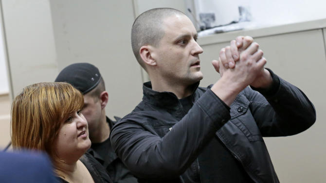 Russian opposition leader Sergei Udaltsov, with his lawyer Violetta Volkova, left, gestures in a courtroom in Moscow, Russia, Saturday, Feb. 9, 2013. Udaltsov, a top Russian opposition figure, has been placed under house arrest for two months, a move that also bans him from using most forms of communication, including the Internet, telephone and mail. A Moscow court imposed the restrictions Saturday after prosecutors complained he had violated a previous agreement not to leave Moscow. (AP Photo/Mikhail Metzel)