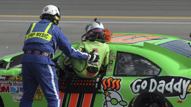 Driver Danica Patrick, right, is helped from her car after a crash during the first of two NASCAR Daytona Duel 150 qualifying auto races in Daytona Beach, Fla., Thursday, Feb. 23, 2012. (AP Photo/Chuck McQuinn)