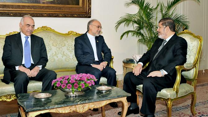 In this image released by the Egyptian President, Egyptian President Mohammed Morsi, right, meets with Iranian Foreign Minister Ali Akbar Salehi, center, and Egyptian Foreign Minister Mohammed Kamel Amr, at the Presidential Palace in Cairo, Egypt, Tuesday, Sept. 18, 2012. (AP Photo/Egyptian Presidency)