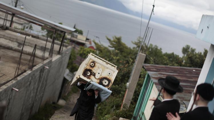 A man from a Jewish community carries a stove near fellow members as they prepare to leave the village of San Juan La Laguna