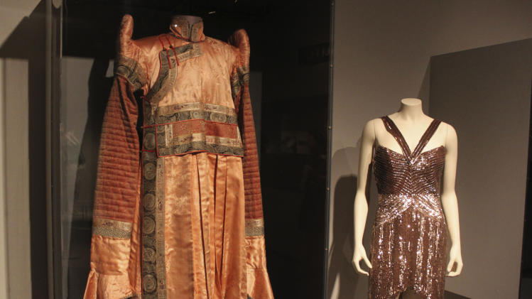 "In this Thursday, Sept. 13, 2012 photo, a brocaded Mongolian silk tunic called a ""deel"" at left is seen next to a sequined chiffon shoulderless cocktail dress from the 2008 fall collection by fashion designer Maria Pinto in the new exhibit ""Fashion and The Field Museum Collection: Maria Pinto"" opening Friday, Sept. 14 at the museum in Chicago. The exhibit features Maria Pinto designs alongside antiquities from the museum. (AP Photo/Caryn Rousseau)"