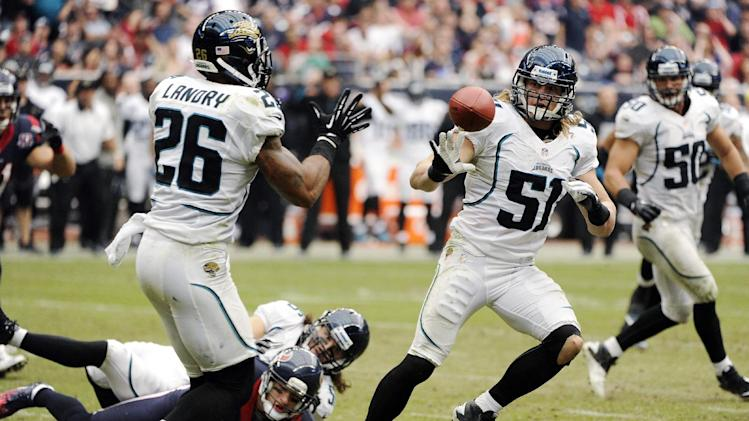 Jacksonville Jaguars' Paul Posluszny (51) tosses the ball to Dawan Landry (26) after intercepting a pass from the Houston Texans during the fourth quarter of an NFL football game, Sunday, Nov. 18, 2012, in Houston. (AP Photo/Dave Einsel)
