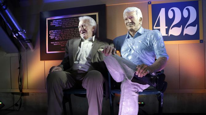 FILE - In this April, 2014 file photo, Milwaukee Brewers radio announcer Bob Uecker sits next to his statue at Miller Park in Milwaukee. Uecker was locked in the radio booth at Miller Park when the door handle broke during the sixth inning against the Dodgers Wednesday night. (AP Photo/Morry Gash, File)