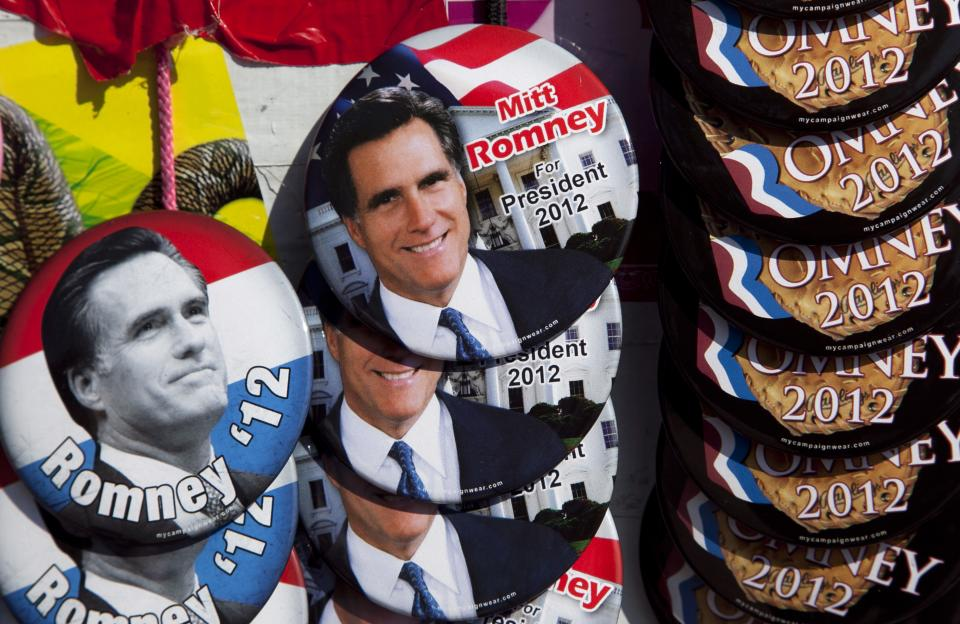 Buttons showing the likeness of Republican presidential candidate, former Massachusetts Gov. Mitt Romney, are seen at a vendor stand outside a Romney campaign event at an oil company in Milwaukee, Monday, April 2, 2012. (AP Photo/Steven Senne)