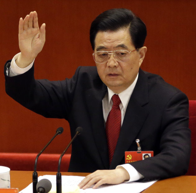 Chinese President Hu Jintao raises his hand to show approval for a work report during the closing ceremony for the 18th Communist Party Congress held at the Great Hall of the People in Beijing, China,