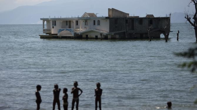 In this Sept. 6, 2012 photo, children stand on the shores of Lake Azuei near a submerged hotel in Thomazeau, Haiti, near the border with the Dominican Republic. The waters' rise has worsened exponentially in recent years, especially after heavy rains in 2007 and 2008 hit the island of Hispaniola. Tropical Storm Isaac dumped more water on the region last month, sparking more damage. (AP Photo/Dieu Nalio Chery)