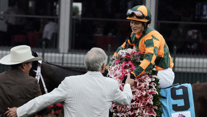 Rosie Napravnik is congratulated by owner Brerton Jones hold up the winning trophy after Believe You Can won the 138th running of the Kentucky Oaks horse race at Churchill Downs Friday, May 4, 2012, in Louisville, Ky. (AP Photo/Garry Jones)