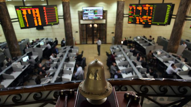 FILE - In this Wednesday, Jan. 2, 2013 file photo, Egyptian brokers work at the stock market in Cairo, Egypt. Egypt's foreign currency reserves fell nearly 10 percent in a single month in January, according to figures released by the central bank Tuesday, Feb. 5, 2013, that provided stark new evidence of a dangerous deterioration in the economy amid political turmoil on the streets. (AP Photo/Khalil Hamra, File)