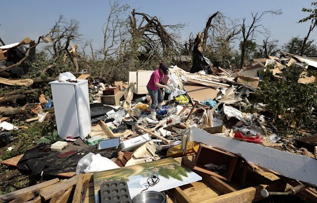 A woman sorts through the debris of a mobile home after it was destroyed by a tornado May 20, 2013 near Shawnee