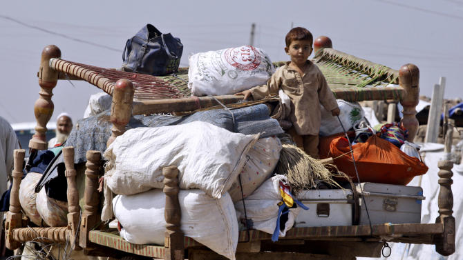 In this Oct. 2, 2012 photo, a Pakistani child who was displaced from Pakistan's tribal areas due to fighting sits on his family's belongings transported on a horse-cart, in Jalozai refugee camp, near Peshawar, Pakistan. Roughly 65,000 refugees from the various tribal agencies are currently living at Jalozai, a Pakistani government camp about 30 kilometers (19 miles) southwest of Peshawar run with the help of international aid agencies. (AP Photo/Mohammad Sajjad)