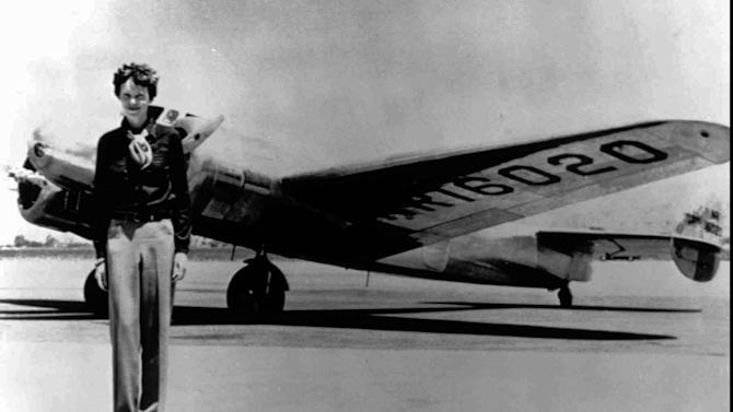 FILE - In this undated file photo, Amelia Earhart stands next to a Lockheed Electra 10E, before her last flight in 1937 from Oakland, Calif., bound for Honolulu on the first leg of her record-setting attempt to circumnavigate the world westward along the Equator. American aviator Earhart's disappearance in 1937 is among aviation's most enduring mysteries. Earhart, the first female pilot to cross the Atlantic Ocean, vanished over the Pacific with Fred Noonan during an attempt to circumnavigate the globe. Seven decades later, people are still transfixed with the mystery. Theories range from her simply running out of fuel and crashing to her staging her own disappearance and secretly returning to the U.S. to live under another identity. (AP Photo/File)