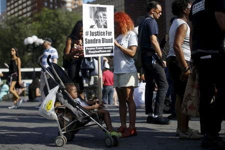 A child holds a sign of Sandra Bland, who died in police custody, during a rally against police violence in New York