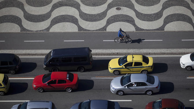 "A man pedals his bike past cars stopped in traffic at Copacabana in Rio de Janeiro, Brazil, Thursday, May 10, 2012. The upcoming Rio + 20 conference, billed as a ""historic opportunity"" to build a greener future, appears to be going up in smoke. President Barack Obama won't be there, and the leaders of Britain and Germany have bowed out. Entire delegations have canceled. The conference is the follow-up to the U.N.'s 1992 Earth Summit, also held in Rio, which helped put climate change on the world agenda. (AP Photo/Felipe Dana)"