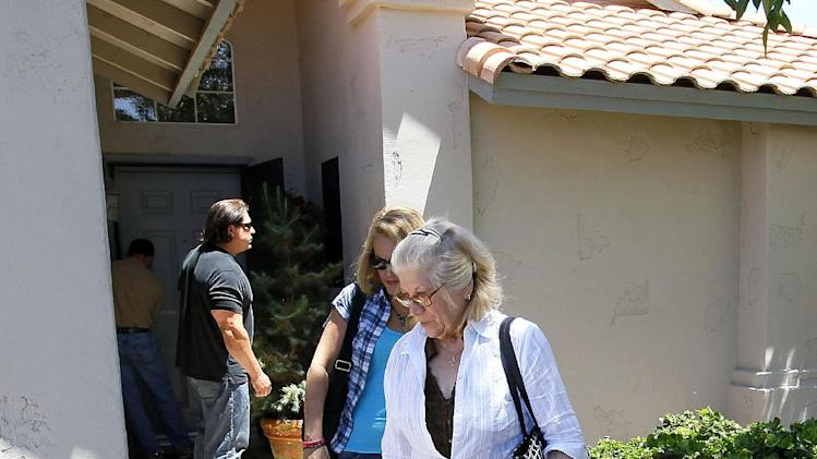People who arrived with Hugo Mederos, father of shooting victim Amber Nieve Mederos, grandfather of 15-month old victim Lilly, Amber's baby, and ex-husband of victim Lisa Lynn Mederos, exit the home of Amber and Lily Thursday, May 3, 2012 in Gilbert, Ariz. Two other people were gunned down alongside Lisa, Amber and Lily in the home. Police have identified one of the five people killed in a shooting in a Phoenix suburb as a former Marine with ties to new-Nazi and Minutemen groups. (AP Photo/Matt York)