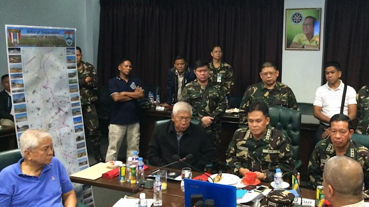 In this handout photo released by the Armed Forces of the Philippines Public Affairs Office, from left seated, Philippine Foreign Affairs Secretary Albert Del Rosario, Philippine National Defense Secretary Voltaire Gazmin and Military Chief General Gregorio Pio P Catapang Jr. conduct an online video conference with 7th Philippine Contingent to Golan Heights commander Lt. Col. Ted Damusmog, as they meet at Camp Aguinaldo military headquarters in suburban Quezon city, Philippines on Saturday Aug. 30, 2014. Philippines Defense Minister Voltaire Gazmin on Saturday said that the country's peacekeepers in Syrian Golan Heights were attacked by a group of Syrian rebels. (AP Photo/Armed Forces of the Philippines Public Affairs Office, HO)