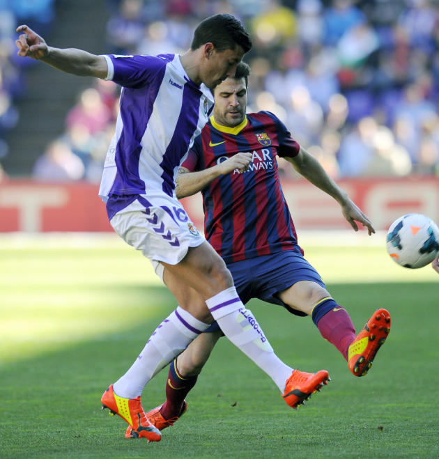Barcelona's Cesc Fabregas, right, challenges Valladolid's Jesus Rueda for the ball during a Spanish La Liga soccer match at the Jose Zorrilla stadium in Valladolid, Spain, Saturday March 8, 20