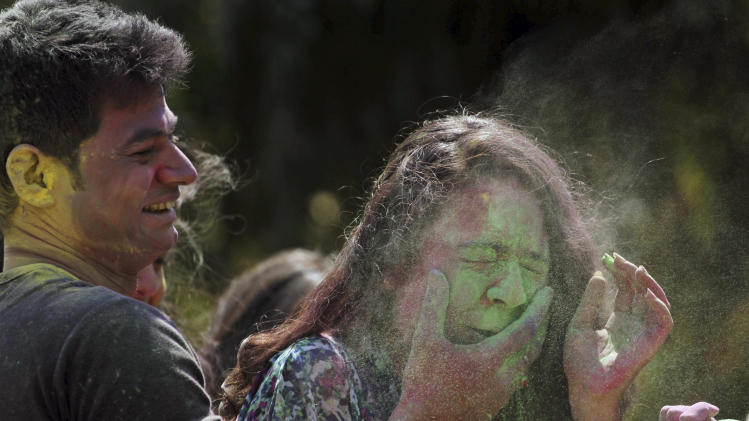 An Indian man smears color on the face of a girl as they celebrate the Holi festival in Ahmadabad, India, Friday, March 14, 2014. Holi, the Hindu festival of colors that also marks the advent of spring, is being celebrated across the country Monday. (AP Photo/Ajit Solanki)